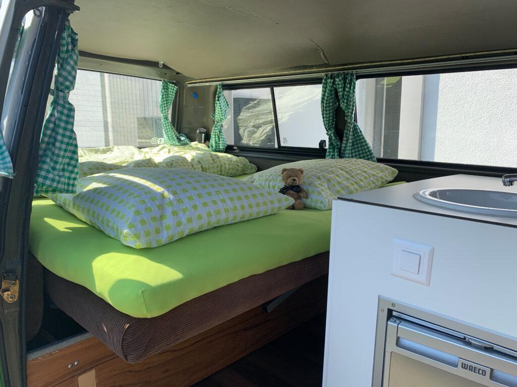 Blick auf das Bett im grünen T3 Campervan